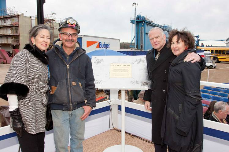 Ann Zumwalt, left, Bath Iron Works welder Carl Pepin, retired Marine Corps Lt. Col. James G. Zumwalt, and Mouzetta Zumwalt-Weathers pose for a photo next to a special steel plate containing the initials of the four children of Adm. Elmo R. Zumwalt during a keel-laying ceremony for the Zumwalt-class destroyer DDG 1000. (U.S. Navy photo courtesy General Dynamics Bath Iron Works, Michael C. Nutter/Released)