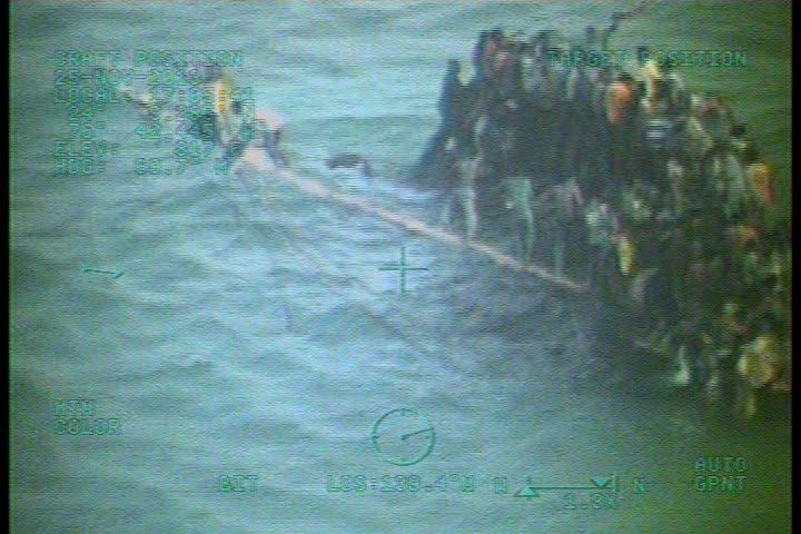 Approximately 100 Haitians sit on the hull of a sail freighter after it grounded and capsized 15 nautical miles southwest of Staniel Cay, Bahamas, Tuesday. A Coast Guard Air Station Clearwater, Fla., MH-60 helicopter crew arrived on scene and hoisted 13 people from the water after deploying a mass rescue raft. U.S. Coast Guard photo.