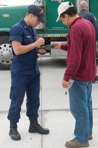 Coastguardsman examining a TWIC credential.