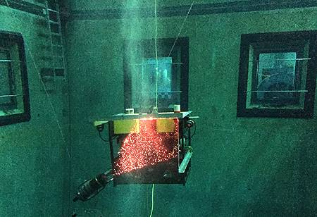 Before operating the MiniROV with its DeepPIV system in the open ocean, MBARI researchers tried it out in MBARI's test tank. In this photograph, you can see bubbles in the water that that are being illuminated by a sheet of light from the laser at lower left. Photo: Paul McGill © 2015 MBARI