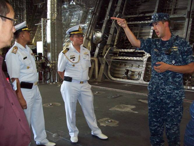 Cmdr. Dave Back (right), executive officer of USS Independence (LCS 2) Gold Crew, conducts a tour of his ship to attendees of the Sea Giraffe Users Group at Naval Base San Diego.  He is seen here showing the ship's spacious mission bay to Cam Fung from Canada (left), and Capt. Charlie Songsawangthus and Cmdr. Sarawoot Chiyangcabut from Thailand. (Photo by Papola Kani, Consulate of Sweden, San Diego)