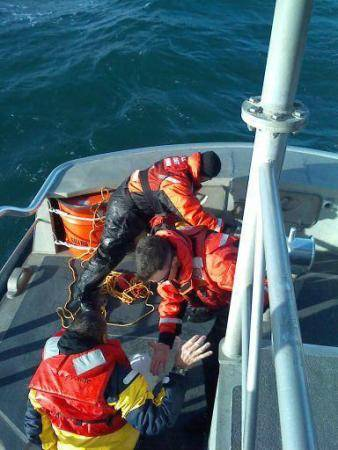 Coast Guard crew members aboard a 47-foot Motor Life Boat from Station Fort Macon help a rescued man to the aft deck. (U.S. Coast Guard photo by Seaman Alyssa Petty)