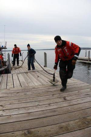 Coast Guard Petty Officer 1st Class Matthew Herrmann, an crew member at Coast Guard Station Portage, Mich., hauls a buoy chain and sinker along the stations pier, Nov. 14, 2013. One of the station's missions is aids to navigation. (U.S. Coast Guard photo by Petty Officer 1st Class Thomas Johnson)