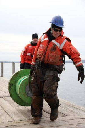 Coast Guard Petty Officer 2nd Class Brandon Cummings, an electrician mate at Coast Guard Station Portage, Mich., hauls a buoy along the stations pier, Nov. 14, 2013. One of the station's missions is aids to navigation. (U.S. Coast Guard photo by Petty Officer 1st Class Thomas Johnson)