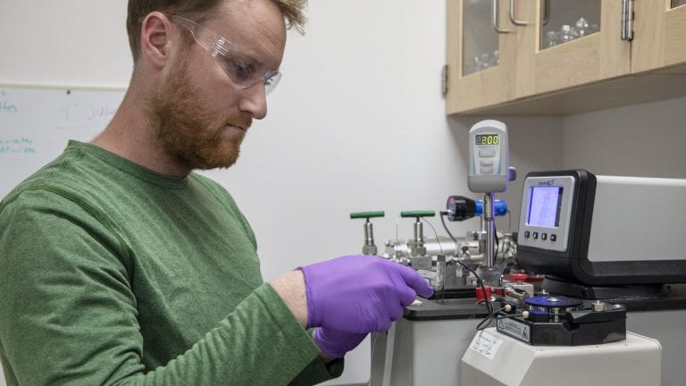 Collin Ward, a marine chemist at WHOI, works on polystyrene samples in his lab. Photo by Jayne Doucette, Woods Hole Oceanographic Institution