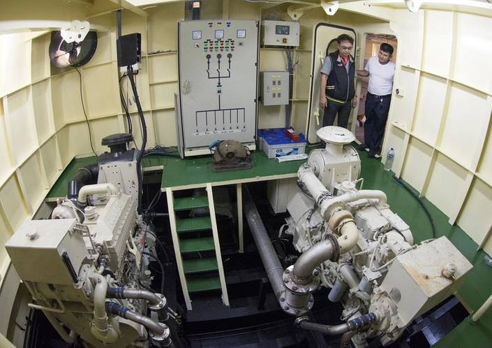 Cummins rep Sathit Suwanprasert checks the Cummins 855-powered gen set with Capt. Mitr in the starboard engine room. (Photo credit: Haig-Brown/Cummins Marine)