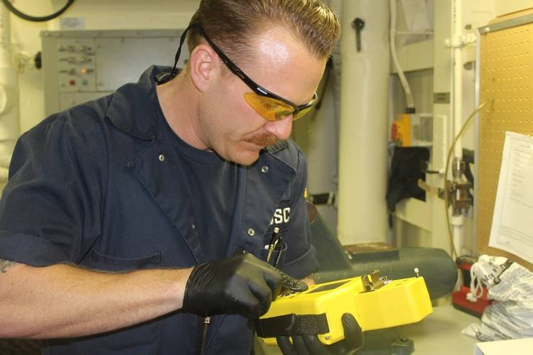 Cutter engineer receives immediate oil analysis results (Photo courtesy USCG)