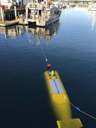 During the 2015 mission to survey the ex-USS Independence CVL 22, the Office of National Marine Sanctuaries' research vessel Fulmar served as the escort boat for Boeing's AUV Echo Ranger. The 67-foot aluminum catamaran research vessel's crew is preparing to tow Echo Ranger to sea. (Credit: Robert V. Schwemmer, NOAA)