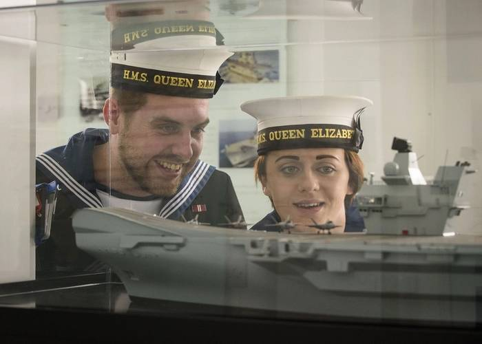 HMS Queen Elizabeth Ship's Company personnel look at a model of the carrier at the new visitor center in Rosyth (Photo: BAE Systems)