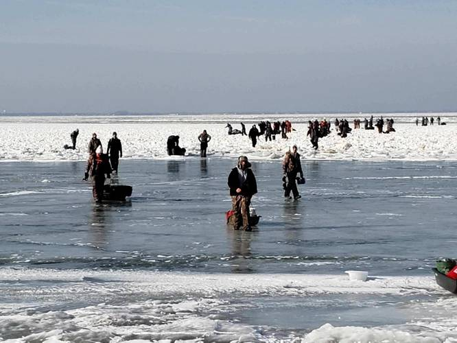 Ice fishermen walk to land after being stuck on an ice floe that broke free from land north of Catawaba Island, March 9, 2019. 46 people were rescued by Coast Guard and local agencies via airboats and approximately 100 people were able to self-rescue by walking across ice-bridges or swimming in the water. (U.S. Coast Guard Photo)