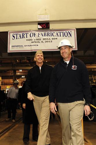 Jim Favreau, director of fabrication at Bath Iron works, leads Chief of Naval Operations (CNO) Adm. Jonathan Greenert during a tour of the shipbuilding facility as Greenert makes his way to the start of fabrication opening ceremony for DDG 1002. Greenert was given the honor of cutting the first piece of steel for the Zumwalt-class destroyer. (U.S. Navy photo by Mass Communication Specialist 1st Class Peter D. Lawlor/Released)