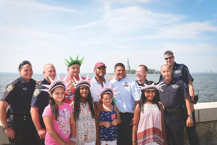 Kevin Suarez, a Dock Attendant for Statue Cruises, reunites with the family he helped rescue when their small boat capsized just off Ellis Island a little over a year ago.