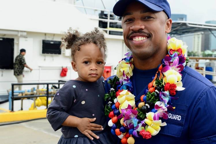 Lt. j.g. Joshua Martin, executive officer, Coast Guard Cutter Joseph Gerczak, holds his daughter following the cutter's arrival Honolulu on February 4, 2018 (USCG photo by Sara Muir)