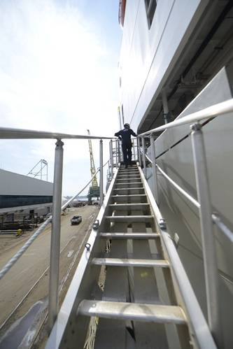 Lt. j.g. Ryan Thomas, a marine Inspector at Coast Guard Sector Delaware, walks up the gangway of the Daniel K. Inouye, a containership being constructed in Philadelphia Shipyards. (Coast Guard photo by Seth Johnson)