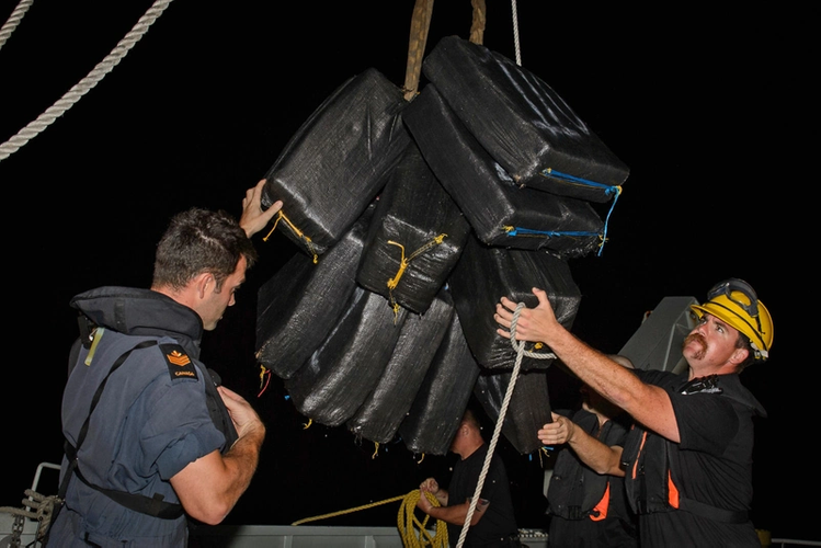 Members of Her Majesty's Canadian Ship NANAIMO transfer cocaine bales seized from a suspected smuggling vessel in collaboration with a United States Coast Guard (USCG) Law Enforcement Detachment during Operation CARIBBE on November 22, 2017. Photo: MARPAC Imaging Services