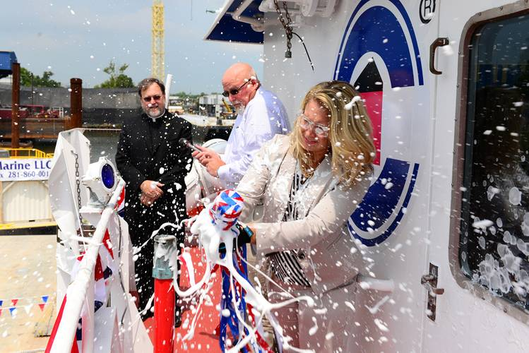Jennifer Legg, Crowley's assistant treasurer and vessel sponsor, breaks the ceremonial bottle of champagne across the hull of the Ocean Sky  the third dynamic positioning (DP) tugboat to the company's expanded ocean towing fleet. (Photo: Crowley Maritime)