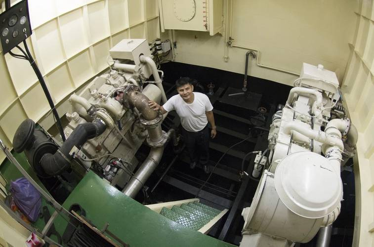 Port Captain Mitr Daiwong standing in the port-site engine room with one of the 600 HP, Cummins KTA19-M main engines. The NT855 150 kW genset is to his left. (Photo credit: Haig-Brown/Cummins Marine)