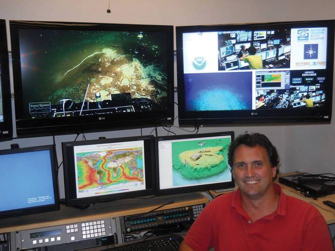 Prof. Dwight Coleman, a marine research scientist at URI's Graduate School of Oceanography, and Director of the Inner Space Center, sits in front of a bank of monitors streaming live video feeds from remote research ships.