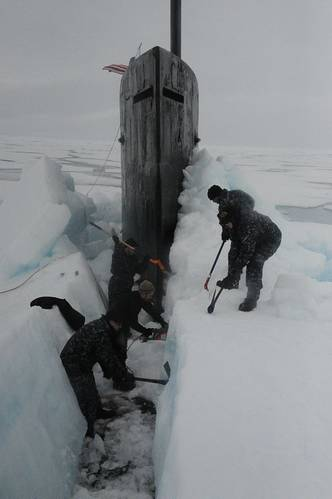 Sailors aboard the fast attack submarine USS Seawolf remove arctic ice from the hull after surfacing at the North Pole. (U.S. Navy photo)