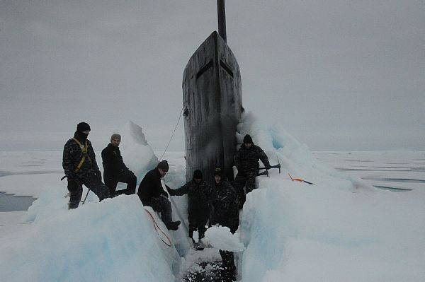Sailors aboard USS Seawolf remove Arctic ice from the hull after surfacing at the North Pole. (U.S. Navy photo)