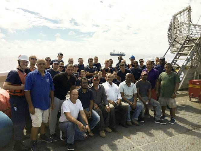 Some of Coast Guard Cutter Confidence's crew gathers with men rescued from the cargo ship Alta. (U.S. Coast Guard photo by Todd Behney)