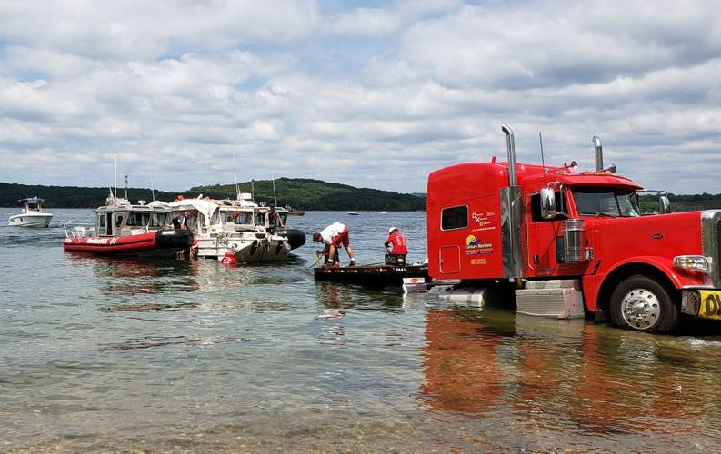 Stretch Duck 7 is loaded onto a flatbed trailer to be transported to a secure facility after being raised from Table Rock Lake in Branson, Missouri, July 23, 2018. The National Transportation Safety Board will take custody of the vessel while investigations continue. (U.S. Coast Guard photo by Lora Ratliff)