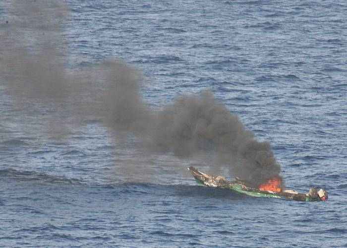 Suspected pirates skiff burns after being destroyed near the amphibious dock landing ship USS Ashland in 2010. (U.S. Navy photo/Harry J. Storms)