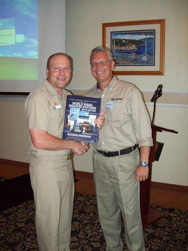 Ted Ackerstierna, Ted Ackerstierna, head of naval domain marketing and sales for Saab Electronic Defence Systems  thanks Captain Winton Smith, commanding officer of the U.S. Naval Base at San Diego, Calif., which served as the host for the 2012 Sea Giraffe Users Group.  Ackerstierna presented a signed copy of Naval Institute Guide to World Naval Weapon Systems by Dr. Norman Friedman.  Dr. Friedman was the keynote speaker for the first day of the three day Sea Giraffe User Group workshop. (Photo