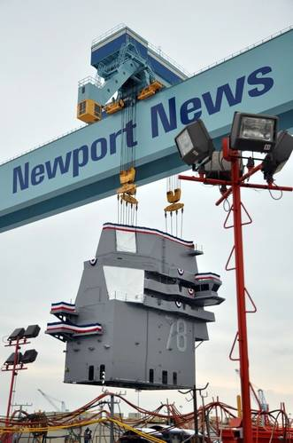 The 555-metric ton island for the future USS Gerald R. Ford (CVN 78) is lifted into position on the ship's flight deck during an island landing ceremony at Huntington Ingalls Industries-Newport News Shipbuilding Jan. 26, 2013. (US Navy photo)