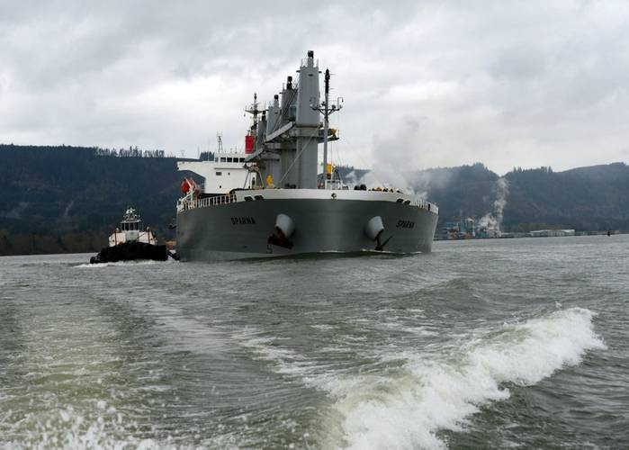 The 623-foot motor vessel Sparna, after briefly running aground and sustaining hull damage a couple days prior, is escorted towards a pier in Kalama, Wash., March 23, 2016. The Sparna suffered multiple fractures along its hull, but no pollution was reported coming from the damaged areas. (U.S. Coast Guard photo by Levi Read.)