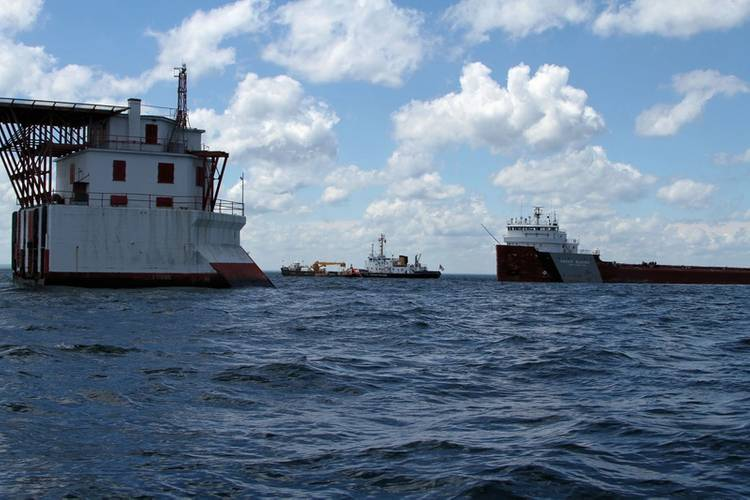 The crew of Coast Guard Cutter Mobile Bay enforces a safety zone alongside the motor vessel Roger Blough, May 29, 2016, in Lake Superior. Crews have been working to salvage the Blough, which ran aground May 27, 2016. (U.S. Coast Guard photo courtesy of Coast Guard Cutter Mobile Bay)