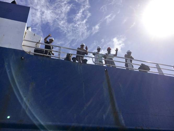 The crew of the disabled cargo ship Alta welcomes the Coast Guard Cutter Confidence's small boat crew as they arrive on scene on October 7. (U.S. Coast Guard photo by Samantha Penate)