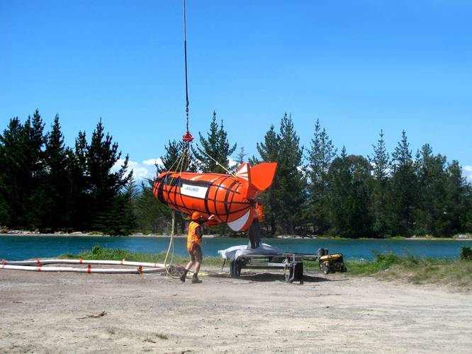 The ShipArrestor container is lifted by the helicopter.