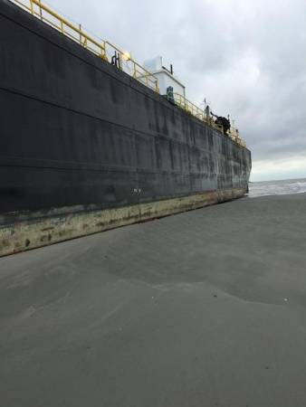 The tugboat, Peter F Gellatly and barge, Double Skin 504, sit grounded near East Beach after high winds pushed it from Bolivar Roads Anchorage, Sunday, Oct. 25, 2015. (U.S. Coast Guard photo by Lt. j.g. In Choi)