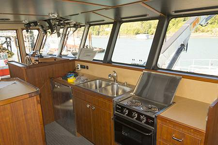 The utilitarian galley is also in the wheelhouse along with a mess table and two bunks