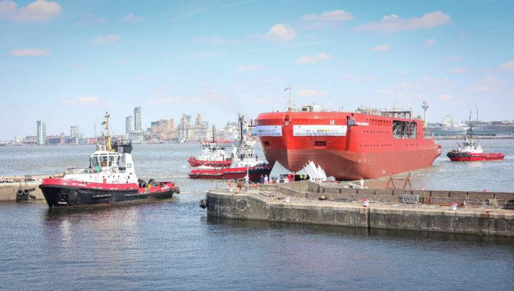 Three tugboats tow the RRS Sir David Attenborough hull into a wet basin for the next stage of construction. (Photo: BAS)