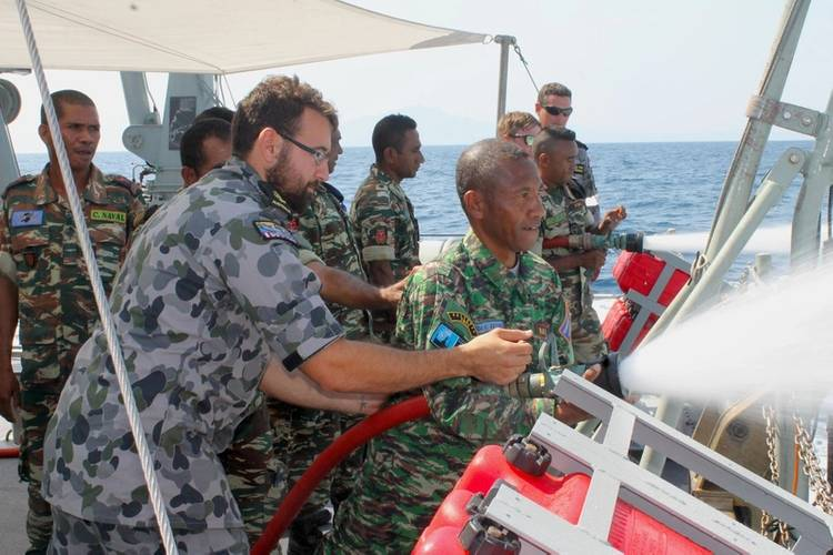 Timor-Leste Defense Force (F-FDTL) members try out HMAS Diamantina's firing fighting equipment during the Minehunter's visit to Timor Leste. (Photo: Ben Catterall)