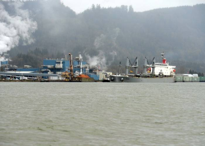 Two tugs support the 623-foot motor vessel Sparna past the Wauna Paper Mill while in transit along the Columbia River to their mooring destination in Kalama, Wash., March 23, 2016. The Sparna, which had briefly run aground Monday morning, was towed to a pier in Kalama to further assess damage and make repairs. (U.S. Coast Guard photo by Levi Read.)
