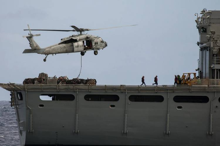 United States Naval Service personnel clear the flight deck of USNS Rainier as their Seahawk helicopter lifts pallets of stores and provisions during a VERTREP (Vertical Replenishment) operation with HMAS Success (Photo: Brenton Freind)