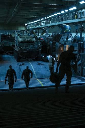 U.S. Marines unload gear from their vehicles in the well deck of the amphibious assault ship USS Essex (LHD 2).  (U.S. Marine Corps photo by Staff Sgt. Joshua Jackson)