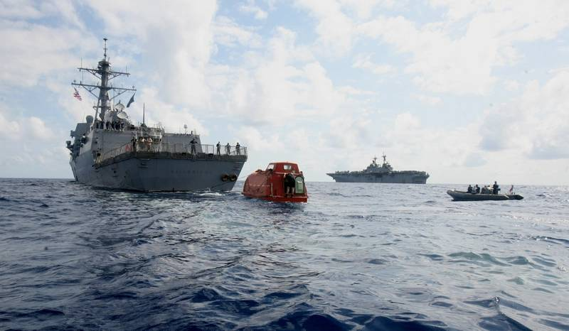 USS Bainbridge tows the lifeboat from the Maersk Alabama to the USS Boxer, in background, to be processed for evidence after the rescue of Capt. Phillips. Phillips was held captive by suspected Somali pirates in the lifeboat in the Indian Ocean after a failed hijacking attempt off the Somali coast. (U.S. Marine Corps photo by Megan E. Sindelar)