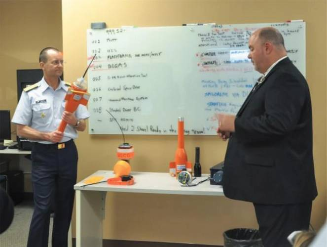 Vice Commandant of the Coast Guard, Adm. Charles Michel, inspects a Maritime Object Tracker Technology (MOTT) while Tim Hughes explains the history and capabilities of the device, during a technology demonstration at Coast Guard Research and Development Center, Thursday, Feb. 15, 2018, in New London, Connecticut. (U.S. Coast Guard Photo courtesy of Research and Development Center)