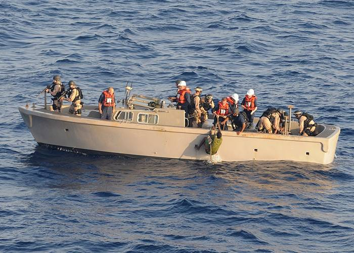 Visit, board, search and seizure team members pull suspected pirates from the sea to be brought to the amphibious dock landing ship USS Ashland. (U.S. Navy photo/ Jason R. Zalasky)
