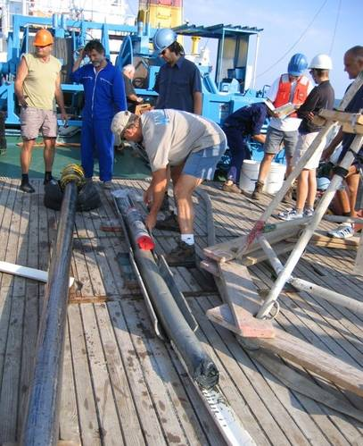 WHOI researcher Alan Gagnon, Marco Coolen (center, in blue safety helmet), and the crew from the Bulgarian research vessel Akademik sample the sediment core that was used for this study. (Photo courtesy Dimitri Dimitrov from the Institute of Oceanology, Bulgarian Academy of Sciences (IO-BAS))