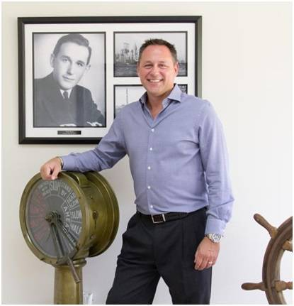 World Wide Metric CEO George Contos stands in front of a picture of his father Constantinos Contos, who founded the company in 1970. George took over as CEO in 2000 and has grown the business significantly since taking the helm. (Photo: World Wide Metric)