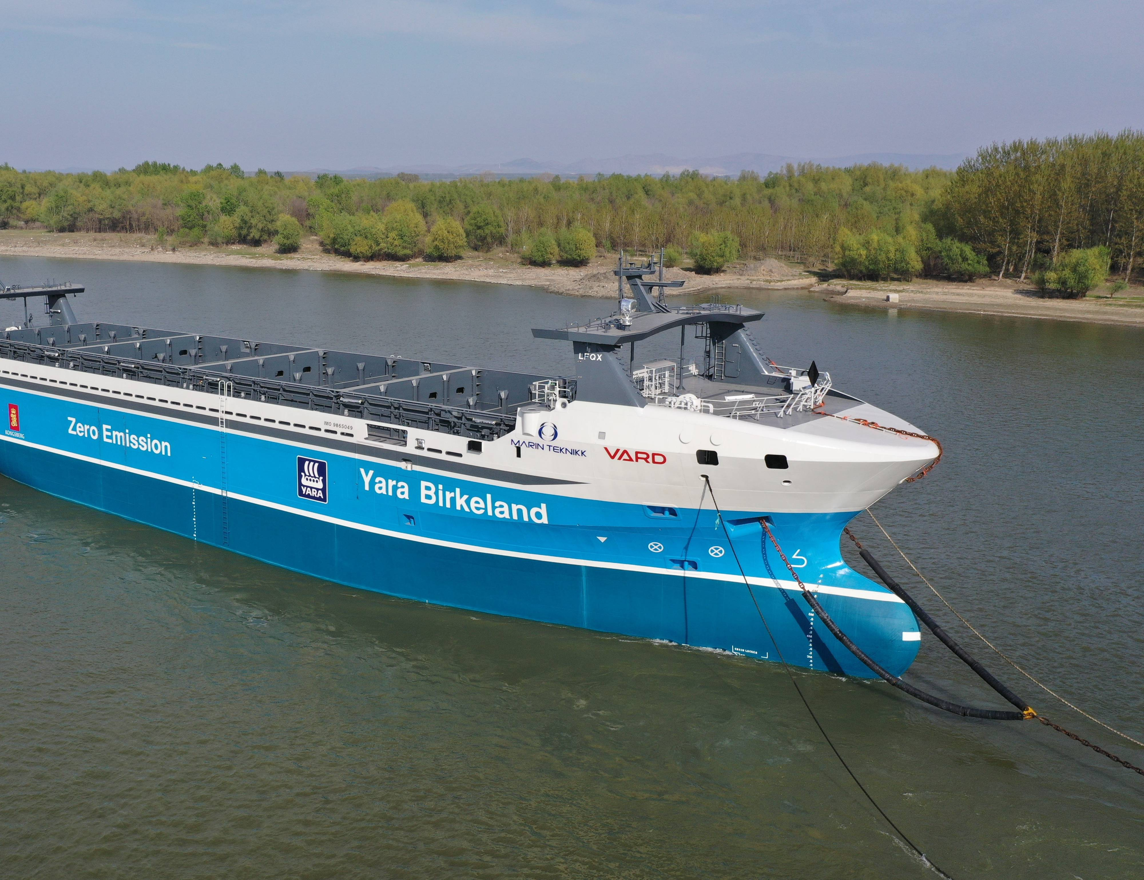 """A fully electric container ship called the MV Yara Birkeland moored in outdoor waters. The ship has its name and the phrase """"Zero Emission"""" printed on its side in large lettering."""